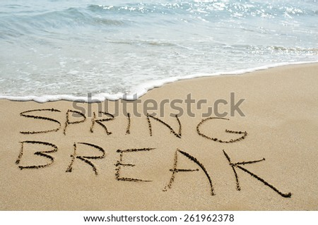 the text spring break written in the sand of a beach - stock photo