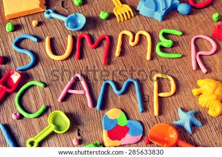 the text summer camp made from modelling clay of different colors and some beach toys such as toy shovels and sand moulds, on a rustic wooden surface - stock photo