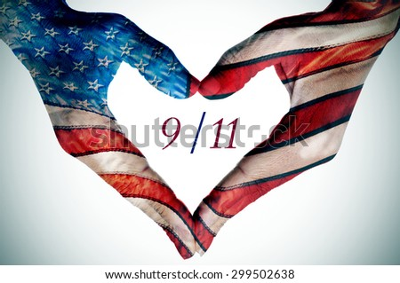 the text 9/11 written in the blank space of a heart sign made with the hands of a young woman patterned as the flag of the United States - stock photo