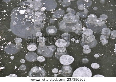 The texture of the first ice. Air bubbles in the ice in late autumn on the pond. - stock photo