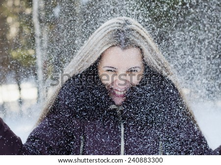 The The beautiful smiling woman has fun throwing snow upwards - stock photo