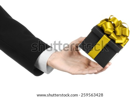The theme of celebrations and gifts: a man in a black suit holding a exclusive gift packaged in a black box with gold ribbon and bow, the most beautiful gift isolated on white background in studio - stock photo