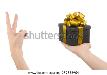 The theme of celebrations and gifts: hand holding a gift wrapped in a black box with gold ribbon and bow, the most beautiful gift isolated on white background in studio - stock photo