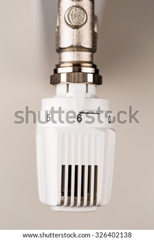 the thermostat of a radiator is on full blast. high room temperature cause high energy costs - stock photo