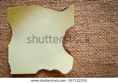 The thick texture of linen cloth on which is a piece of paper. Macro. - stock photo