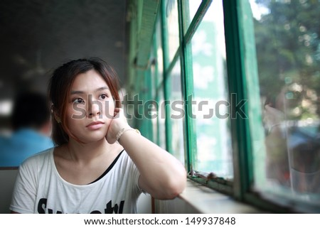 The Thinker, annoying woman waiting someone look at window, staring into space, fall into a trance - stock photo
