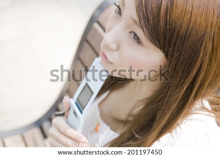 The thinking woman by supporting her jaw with a mobile phone on the bench - stock photo