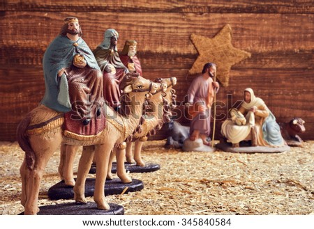 the three kings on their camels and the holy family in a rustic nativity scene - stock photo