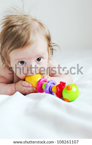 The three-month baby playing with a toy