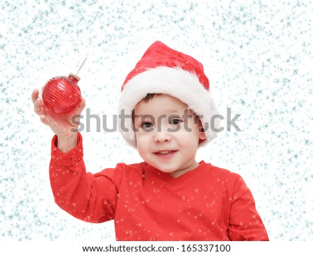 the three-year-old kid considers a fir-tree sphere and snowflakes  - stock photo
