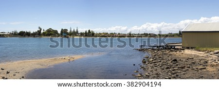 The tide ebbs out on the  Leschenault Estuary near the  cycleway  in Bunbury Western Australia on a cool sunny afternoon in spring leaving the mud flats exposed.
