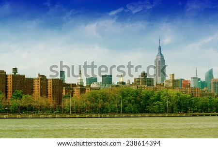 The tight cluster of skyscrapers habituating midtown Manhattan with the famous Empire State Building most prominent, as seen from East River. - stock photo