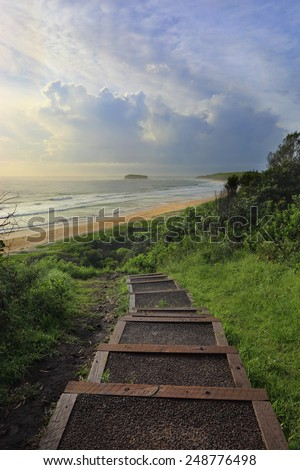The timber and bitumen  path abruptly ends from the headland at Mystics Beach in Killalea State Park, then you make your own way down through the trees and vegetation.  - stock photo