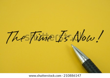 The Time Is Now! note with pen on yellow background