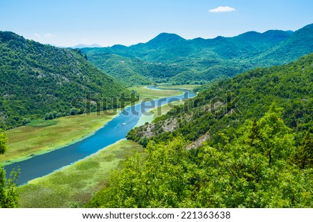 The tiny boat sails through the Crnojevica river, one of the most beautiful places in Montenegro. - stock photo