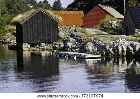 The tiny fishing village of Oygarden, Norway, with typical red buildings - stock photo