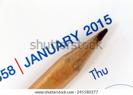 The tip of a pencil point to the year 2015 text on a calendar.