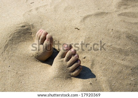 The toes of feet which are sticking out of sand