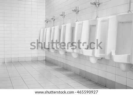 The toilet of man with toilet view by urinals , interior at the old toilet background in black and white tone