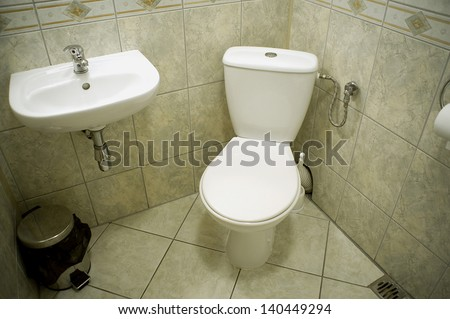 The toilet room with a toilet bowl and a wash basin - stock photo