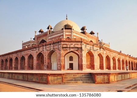 The Tomb built with red sandstone follows a highly symmetric design, Humayun's Tomb, Delhi. An angular view shows the tomb's raised platform and its row of arches.