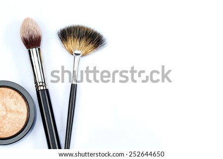 The tools for constructing beauty. Closeup of two professional makeup brushes and a loose cosmetic powder spread against white background with copy space - stock photo