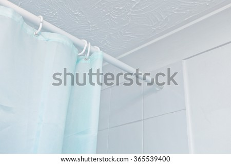 The top of a blue shower curtain hanging on a rail