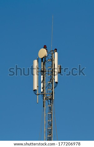 The top of a cell phone tower - stock photo