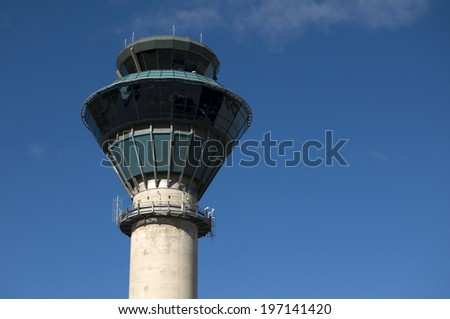 The top of an airport control tower against a blue sky.