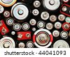 The tops of batteries are shown with different sizes and charges. There is an abstract color and texture to the photo. - stock
