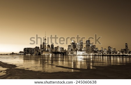The Toronto Skyline in the Winter from the East at sunset showing the frozen lake and patches of snow on the ice - stock photo