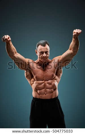 The torso of attractive male body builder on gray background.