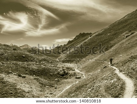 The tourist on the moraine of the glacier Gokyo in the area of the Cho Oyu (8153 m) - Nepal, Himalayas (stylized retro) - stock photo