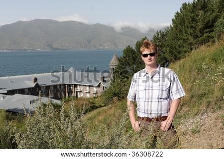 The tourist poses on the monastery background, Armenia - stock photo
