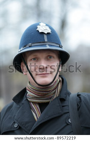 The tourist posing in british police hat - stock photo