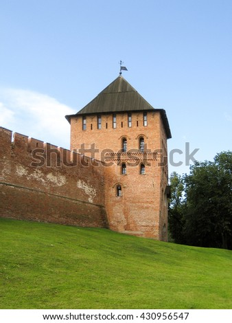 The tower and part of the walls of the ancient Kremlin in Veliky Novgorod, made of red bricks, located on a green hill.