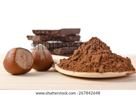 the tower from chocolate with nuts  and cacao powder in the wooden spoon on wooden table - stock photo