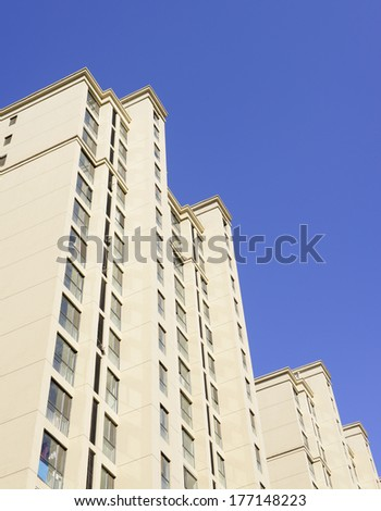 The towering apartment building under the blue sky