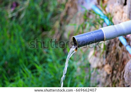 The toxic water flowing from the small sewer water or pipe into the floor with soft blur background