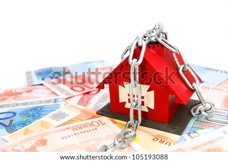 The toy house and chain with money. On a white background. - stock photo