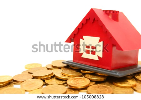 The toy house on gold coins. On a white background.