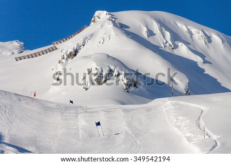 The track giant slalom on the background of snow-capped mountains in the bright sun.