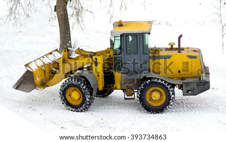 the tractor loads the cleaned snow on the dump truck
