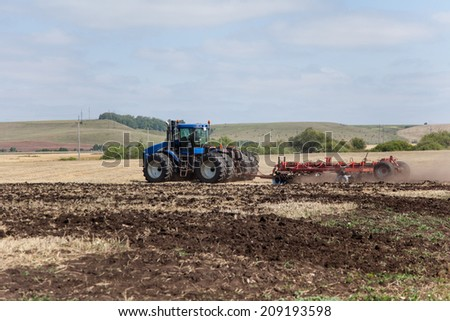 the tractor plowing a field - stock photo