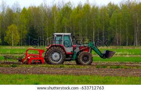 The tractor sprinkles the spring field.