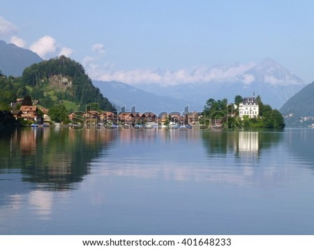 The Traditional fishing village of Iseltwald, Switzerland reflected in the still waters of Brienzersee Lake, with Niesen Mountain in the background