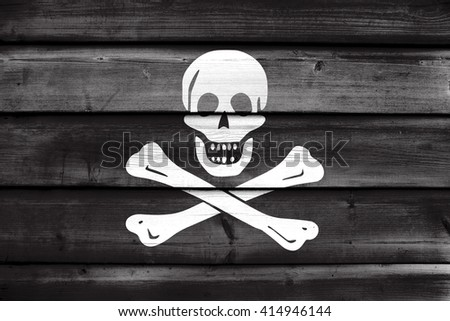 The traditional Jolly Roger of piracy Flag, painted on old wood plank background - stock photo
