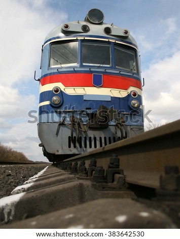 the train on the rails on a background of blue sky with clouds