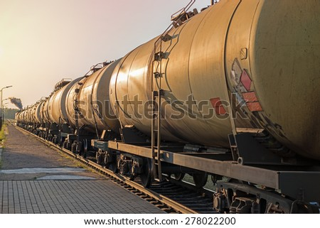 The train tanks with oil and fuel at sunset - stock photo