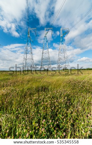The transmission lines in green field in summer